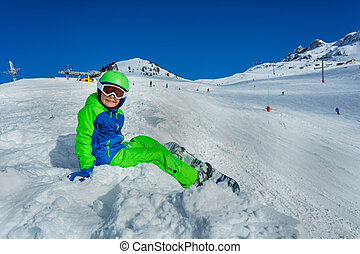 Side portrait of little boy in snow with snowboard