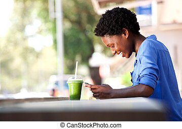 smiling african american woman reading text message on mobile phone at cafe