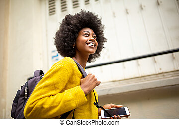 smiling african american woman with bag and mobile phone walking in city