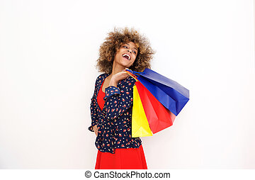smiling young african american woman holding shopping bags and laughing