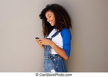 portrait of smiling young african american woman looking at cellphone