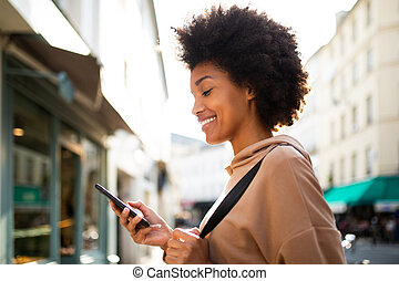 Side portrait of smiling young black woman looking at mobile phone in city