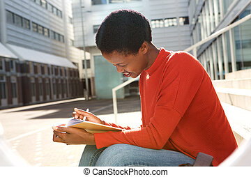 smiling young woman writing in book outside