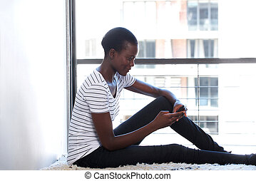 young african american female using mobile phone by window at home