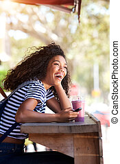 young african american woman laughing with cellphone at cafe