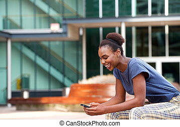 Side portrait of young african american woman looking at mobile phone outdoors