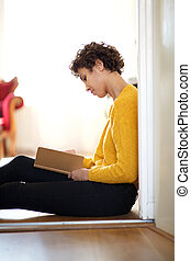 young african american woman sitting on floor with book
