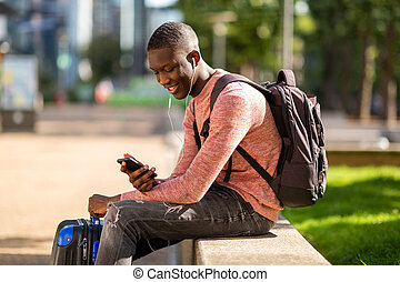young african man sitting outside with travel bags and mobile phone