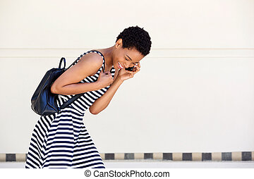 young african woman laughing with cellphone and bag