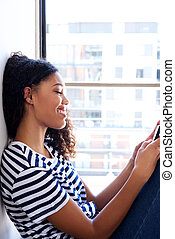 young black woman looking at mobile phone