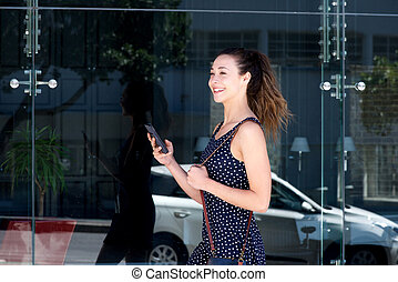 young happy woman walking outside with smart phone