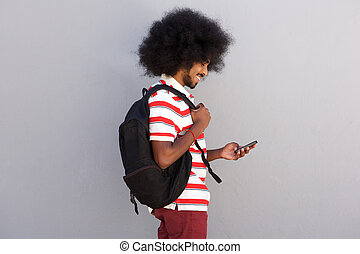 young man with afro and mobile phone smiling