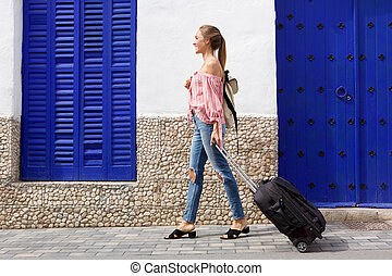 Side portrait of young travel woman walking on street with suitcase