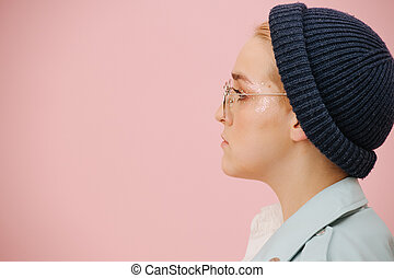 Side portrait of young woman in a cap, round glasses with serious face.