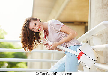 young woman with bag laughing outside
