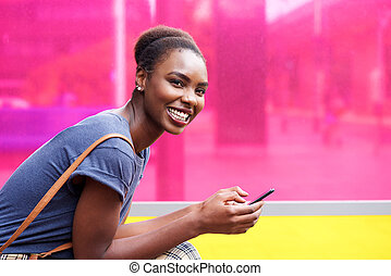 smiling african american woman holding mobile phone