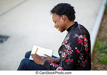 smiling young african woman sitting outside writing in book
