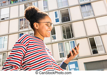 smiling young black girl standing outside looking at mobile phone