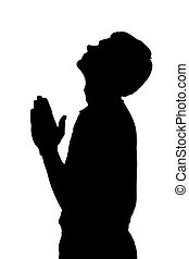 Side profile portrait silhouette of religious teenage boy praying with raised head