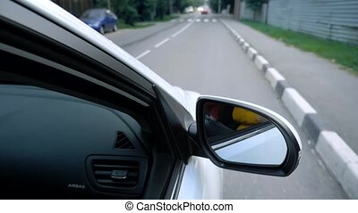 side rear-view mirror of a car while driving on a highway.