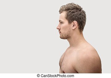 Side shot of young man. He is emotionless. Isolated on white...