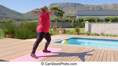 Side vie of old asian senior woman exercising in the ...