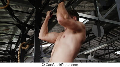 Side view close up of a shirtless athletic Caucasian man cross training at a gym, doing chin ups holding onto a bar