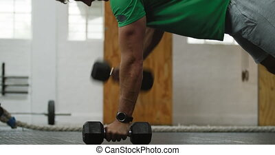 Side view athletic Caucasian man lifting alternate weights...