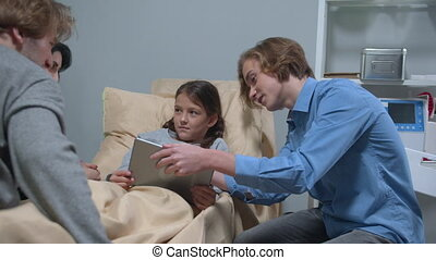 Side view, boy show something on tablet to girl who lie on the bed in the hospital
