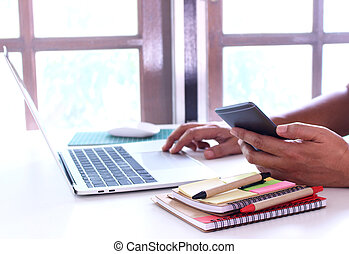 side view, business man holding smartphone .office table desk. workspace with notebook and mouse on copy space