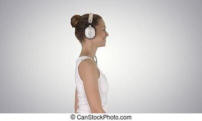 Happy casual girl wearing headphones walking on gradient...