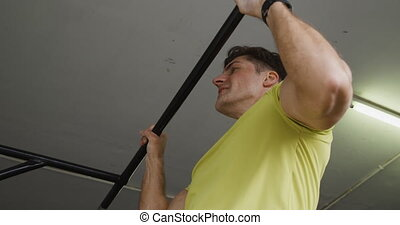 Side view close up of an athletic Caucasian man wearing sports clothes cross training at a gym, doing chin ups holding onto a bar