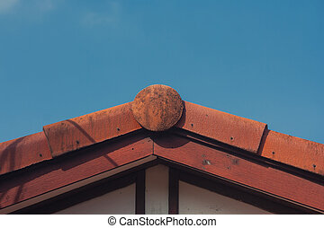 Side view close up of tiled roof on top of house with blue sky in the background in vintage style.