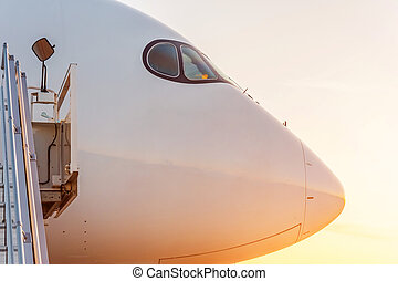 Side view close up on the nose of a passenger plane at sunset.