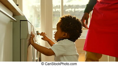 Side view cute little black son playing at washing machine in kitchen of comfortable home 4k