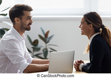 Side view diverse consultant and client sitting at desk