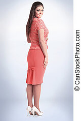 side view. fashionable woman model in red dress looking at camera .