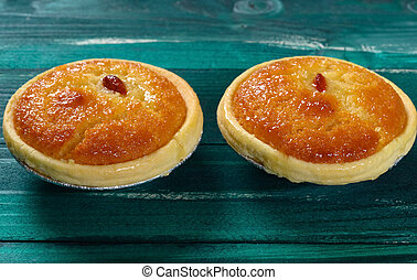 side view fresh cocknut tarts on green wood table