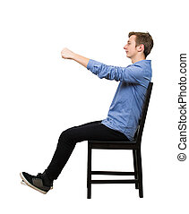 Side view full length portrait of confident teenager boy dreamer pretend to drive an imaginary transportation, car or bike, while sitting in his chair isolated over white background.