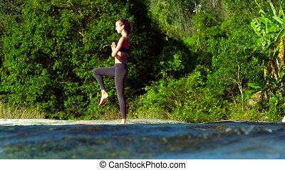 side view girl stands in yoga pose Tree on stream bank