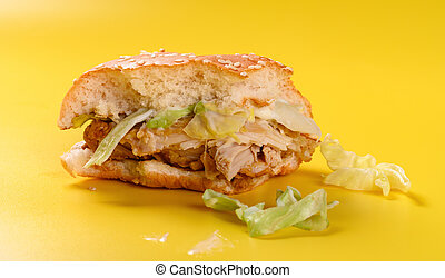 side view half eaten hamburger on a yellow background