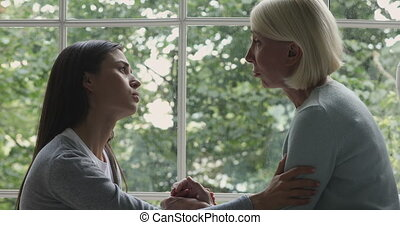 Side view head shot supportive loving grownup daughter stroking arm of desperate stressed middle aged mother, sitting near huge window. Young kind caring woman showing support to mature elderly mom.
