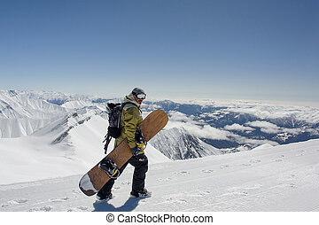 Side view manful snowboarder walking with the snowboard in ...