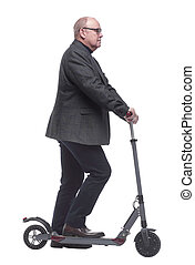 side view . Mature man with electric scooter looking forward