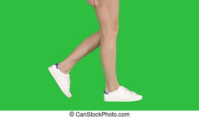 Women feet wearing white sneaker shoes walking on a Green...
