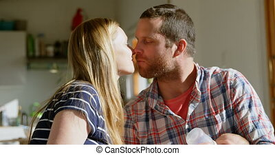 Side view mid adult caucasian parents kissing each other in ...