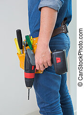 Side view mid section of a handyman with drill and toolbelt...