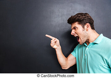 Side view of a angry man screaming over black background