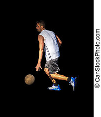 Side view of a basketball player dribbling on black
