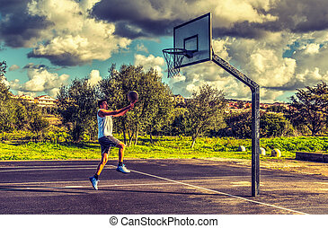 Side view of a basketball player lay up